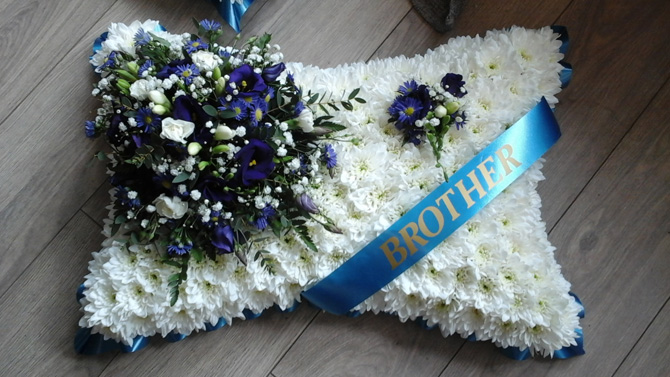 Pillow shaped funeral flowers brother sash white blue Bristol florist FPI1