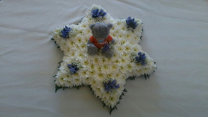 Star shaped funeral flowers teddy white blue florist north Bristol FST4